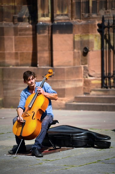A celloist performs in front of the Notre-Dame de Strasbourg